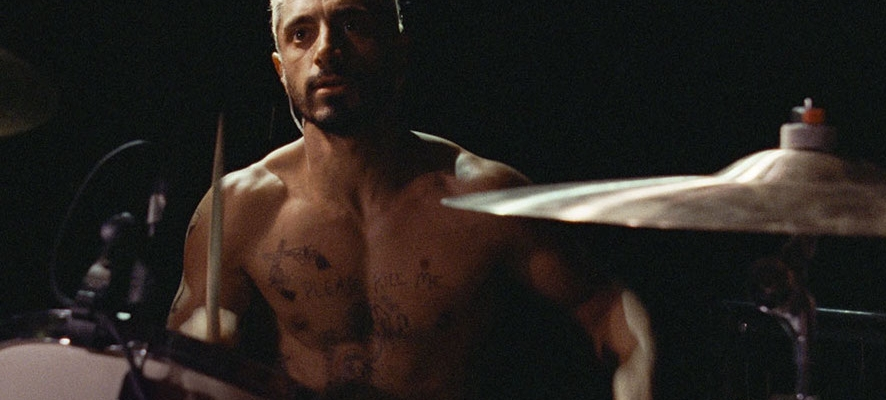 A shirtless man plays the drums, staring offscreen. Behind him, there is only blackness.